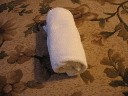A rolled towel for neck and headache relief.